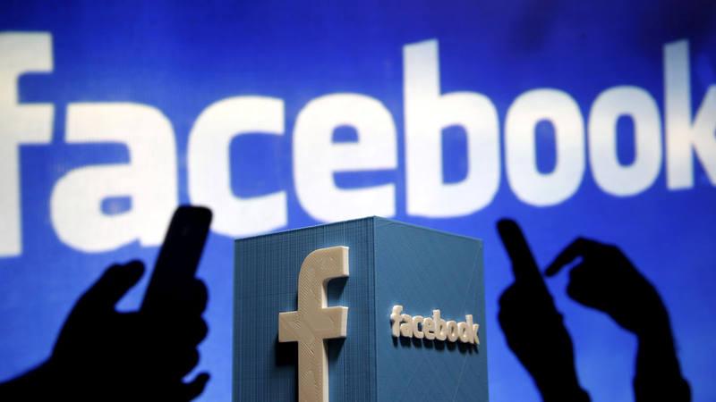Un atril con el logo de Facebook delante de una pantalla