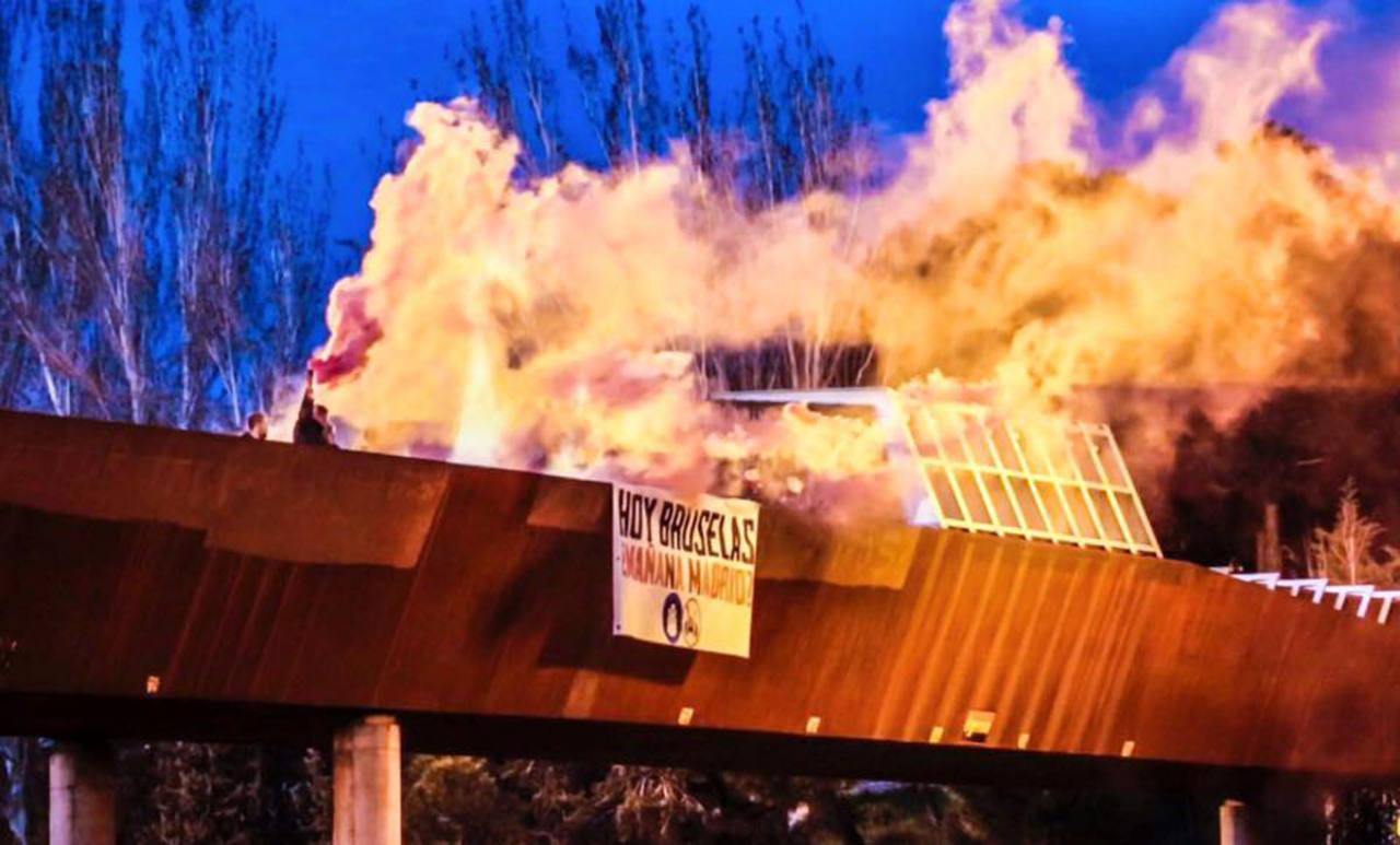 """Bengalas ardiendo y una pancarta en la que pone: """"Hoy Bruselas, ¿mañana Madrid?"""", obra del grupo Hogar Social Madrid, junto a la mezquita de la M-30."""