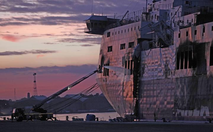 Un bombero apaga los focos aún sin extinguir del ferri 'Norman Atlantic', en el puerto italiano de Bríndisi.