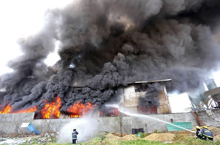 Bomberos intentan apagar el fuego en la fábrica de Manila (Filipinas) en la que han perecido varios trabajadores