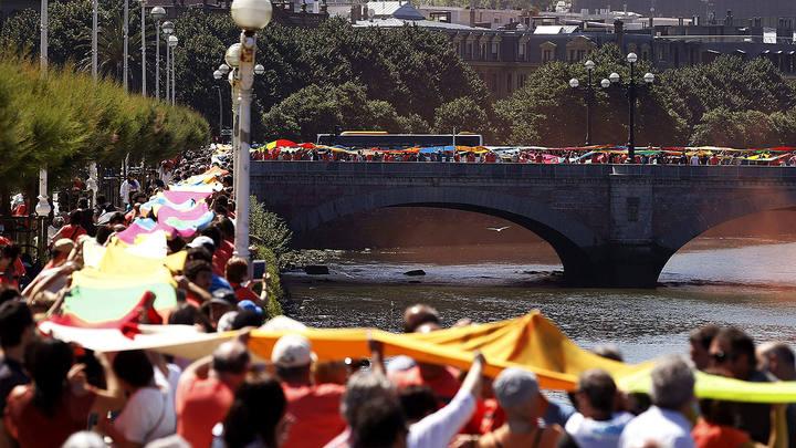 Una cadena humana de telas une los seis puentes sobre el río Urumea en San Sebastián