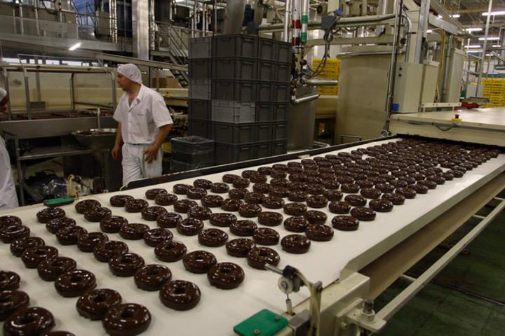 Cadena de producción de dónuts de chocolate en Panrico