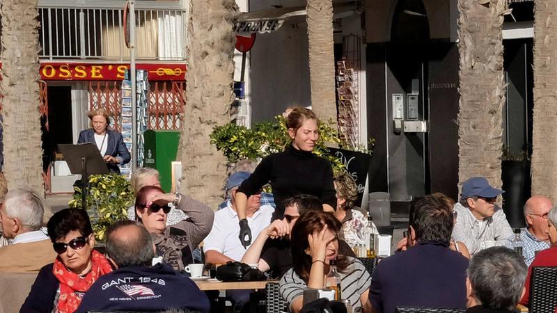 Una camarera sirve mesas en una terraza en Benidorm