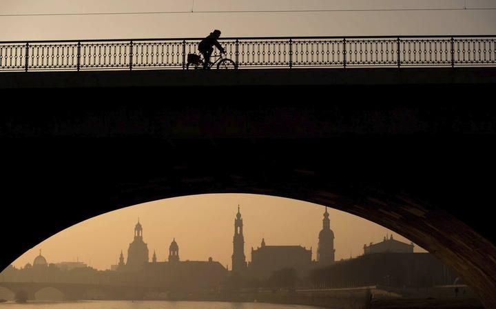 Un ciclista cruza el puente Marien al amanecer en Dresde