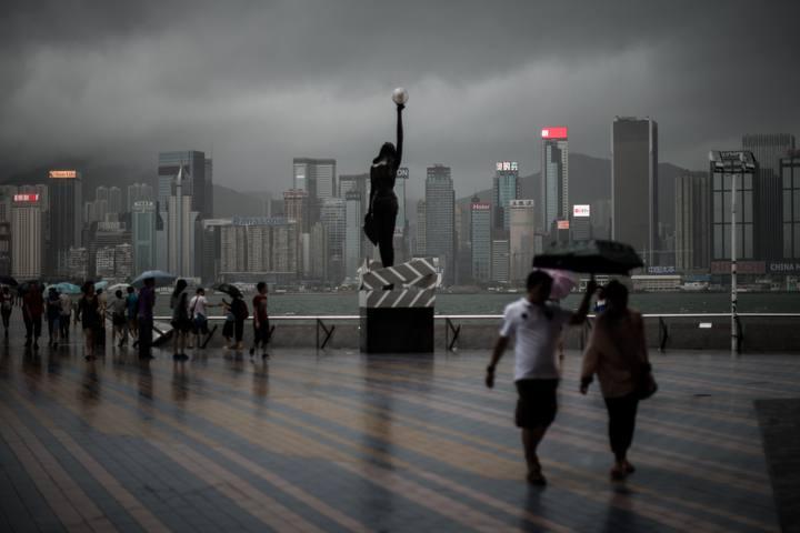 Ciudadanos de Hong Kong andando bajo la tormenta provocada por el superifón Rammasun