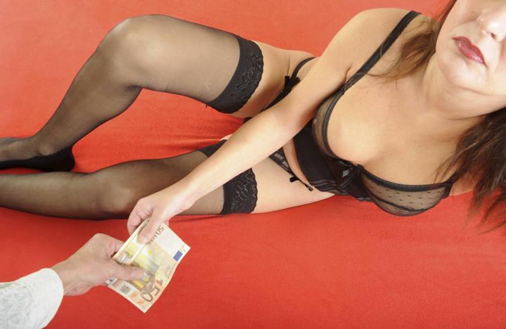 Un cliente paga con un billete de 50 euros a una prostituta