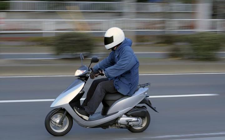 Conductor de scooter con un casco puesto.