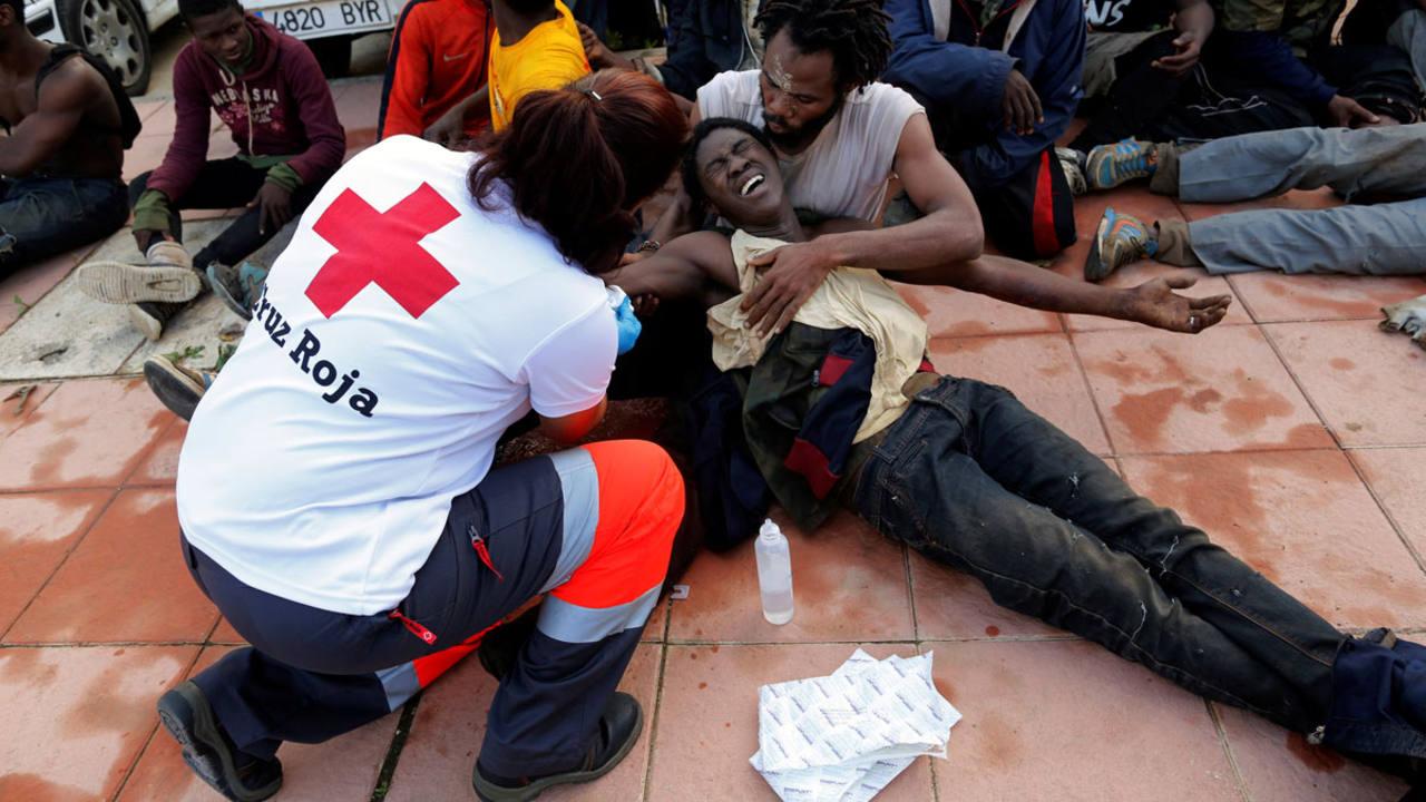 Un trabajador de la Cruz Roja asiste a uno de los inmigrantes que han saltado la valla fronteriza en Ceuta
