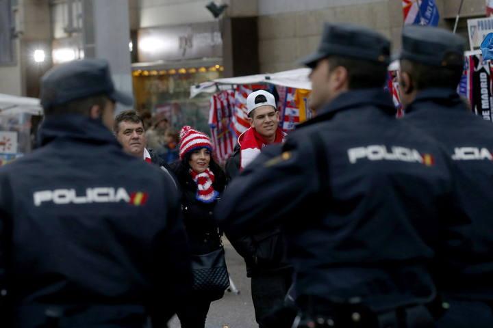 Dispositivo policial ante unos aficionados rojiblancos en el exterior del estadio Vicente Calderón, en Madrid.