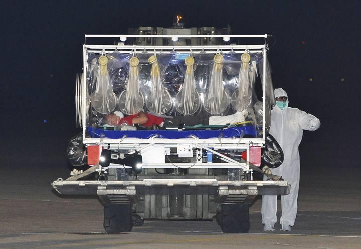 El doctor italiano infectado de ébola es trasladado en una camilla aislada a su llegada al aeropuerto de Pratica di Mare, cerca de Roma