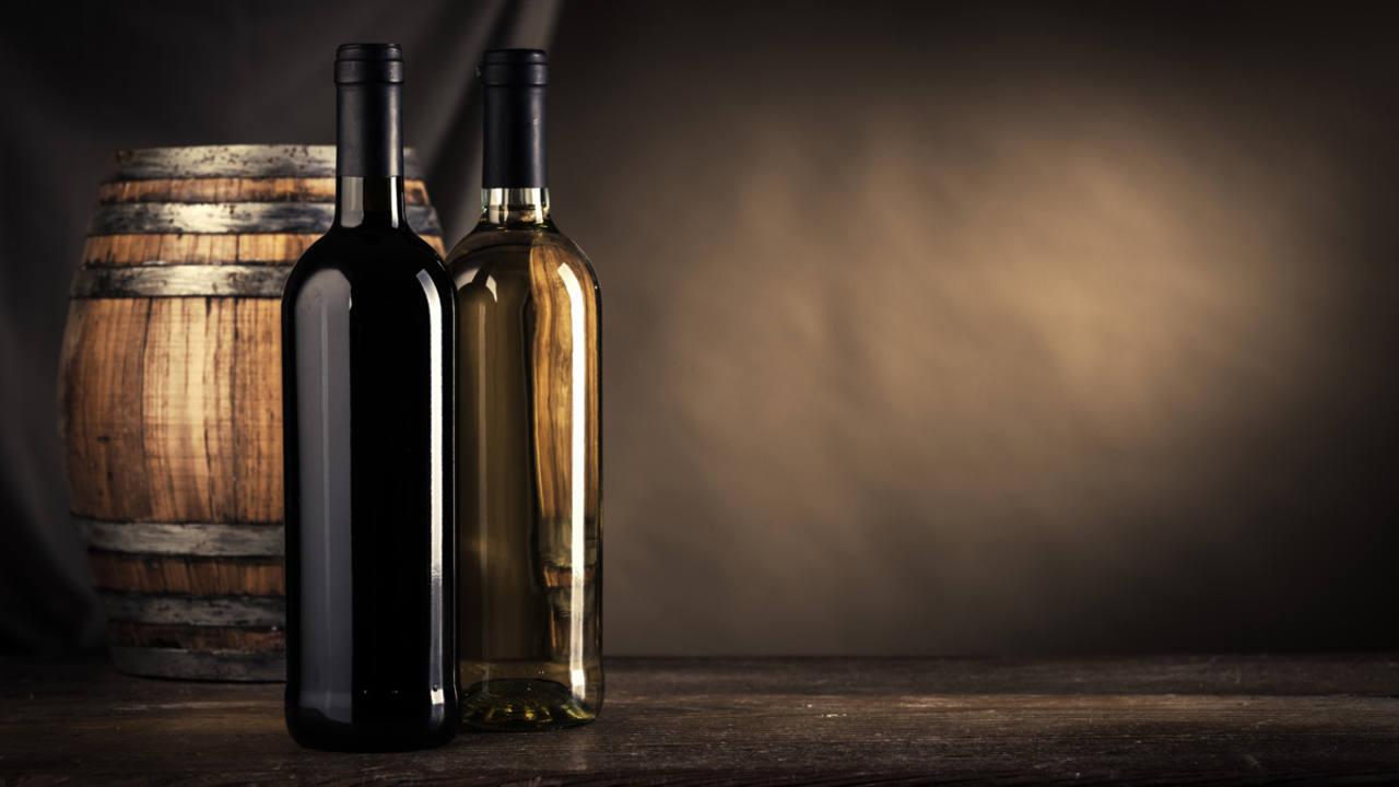 Dos botellas de vino delante de una barrica