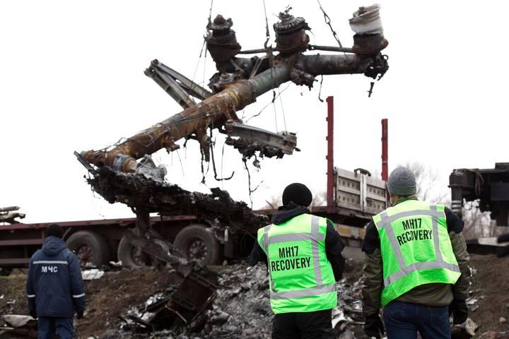 Dos miembros del equipo de expertos holandeses miran cómo retiran varios restos del Malaysia Airline, Grabove (este de Ucrania).