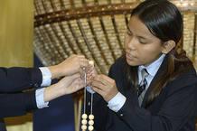 Dos niñas introducen las bolas en los alambres
