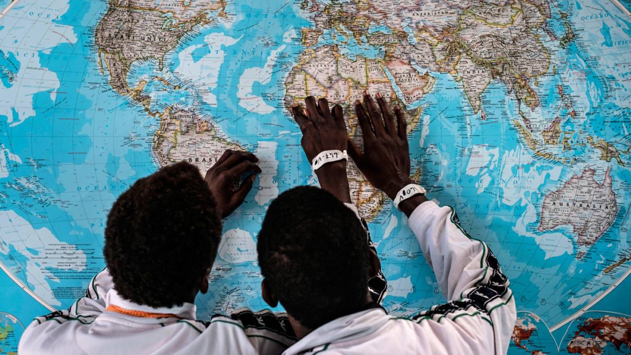 Dos niños refugiados de Gambia consultando un mapa el 17 de mayo 2016, en el Puerto de Pozzallo en Sicilia, Italia.