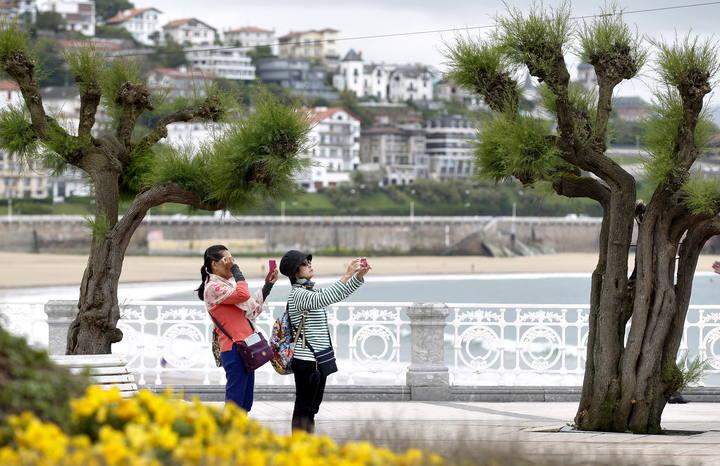 Dos turistas fotografían el parque Alderdi Eder de San Sebastián