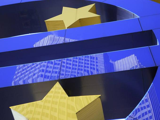 El edificio del Banco Central Europeo reflejado sobre el símbolo del euro, en Fráncfort