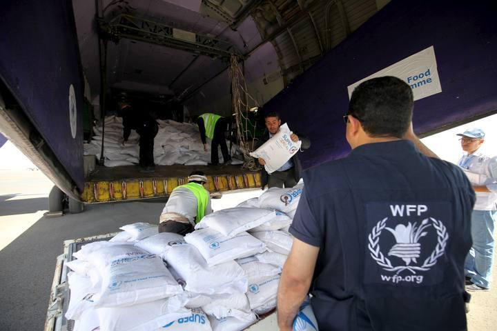 Empleados del Programa Mundial de Alimentos descargan ayuda humanitaria en Saná, capital de Yemen