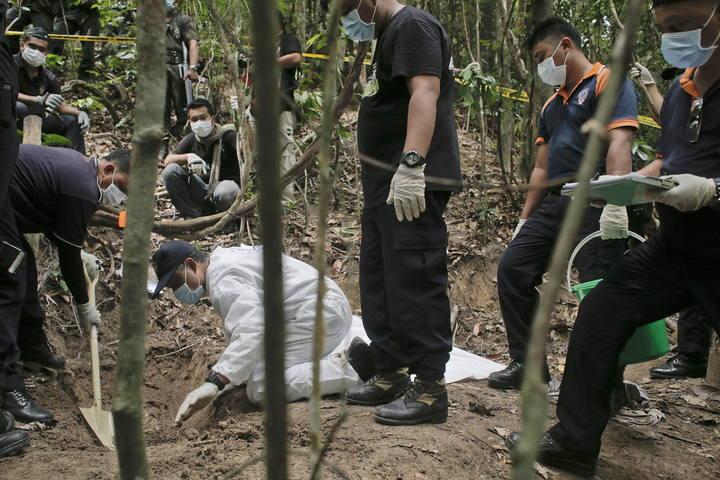 Un equipo de la policía forense malasia excava una fosa descubierta en las colinas Wang Burma en Wang Kelian, Perlis (Malasia)