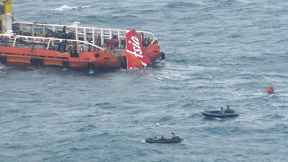 Los equipos de rescate sacan del mar la cola del avión de AirAsia