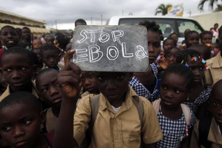Un estudiante lleva un cartel en el que pide que pare la epidemia de ébola.