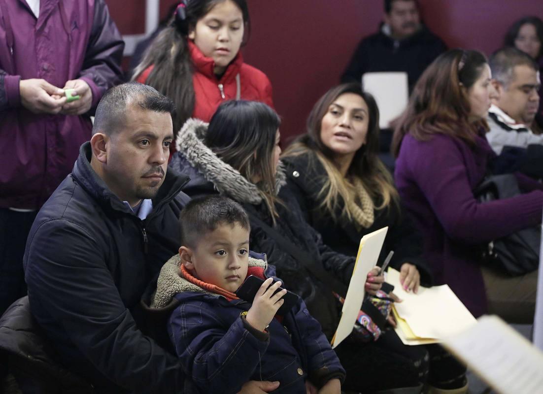 Un familia de inmigrantes latinos asiste a un taller de asesoría legal en una iglesia del sur de Chicago