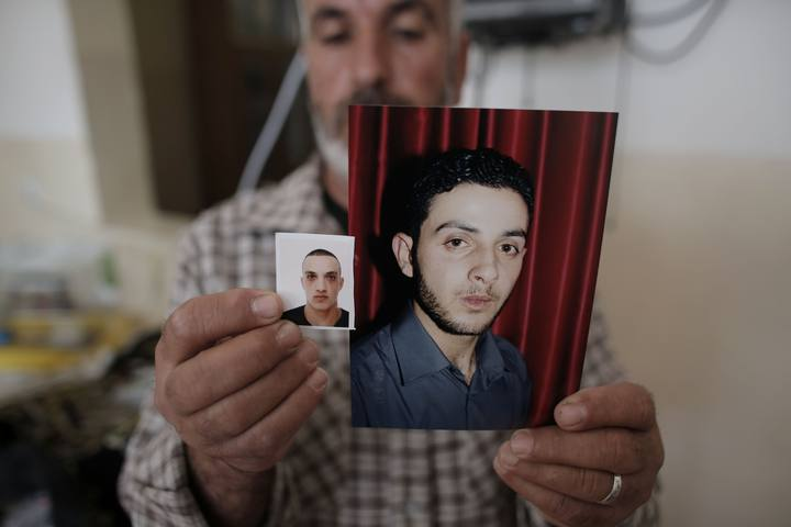 Un familiar de Uday (izda) y Ghasan Abu Yamal (dcha) muestra sus fotografias. Foto: AFP PHOTO / AHMAD GHARABLI