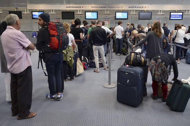 Fila de viajeros ante los mostradores de facturación del aeropuerto de Marsella