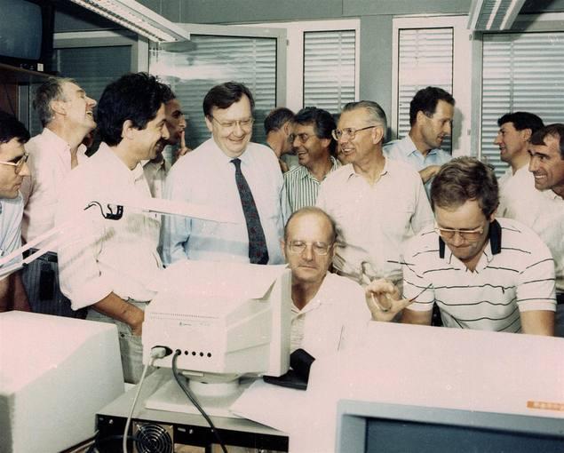 Físicos mirando una pantalla de ordenador de la sala de control del LEP