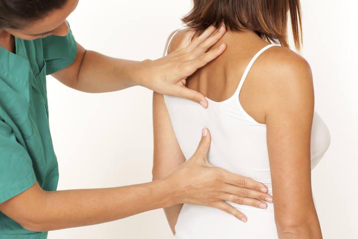 Una fisioterapeuta haciendo un masaje a una paciente.