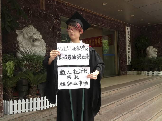 """Fotografía de archivo de la activista feminista Zheng Churan. En el cartel se lee: """"Las mujeres licenciadas tienen talento, contratar solo a hombres es frustrante"""""""