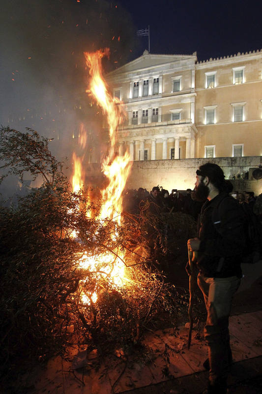Ganaderos y agricultores queman ramas de olivo frente al Parlamento en Atenas