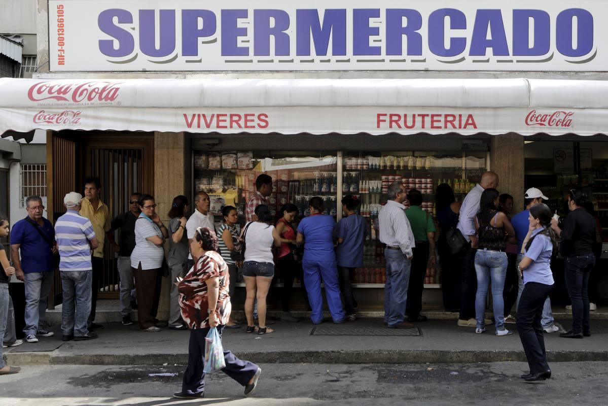 La gente hace cola en un supermercado de Caracas para adquirir productos básicos