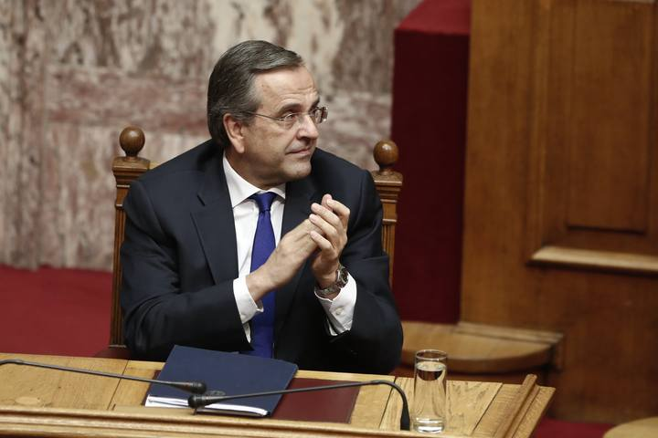 Greece's Prime Minister Samaras applauds a lawmaker before a confidence vote for the country's coalition government in Athens