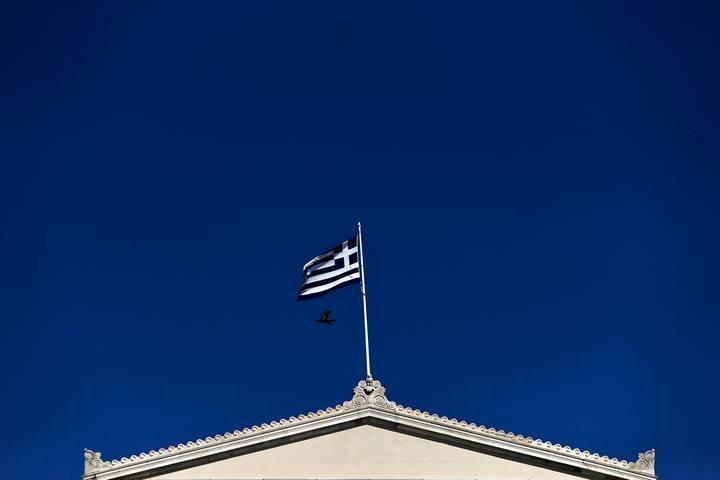 A Greek national flag flutters atop the parliament building in Athens. Imagen de la bandera griega sobre el parlamento heleno.