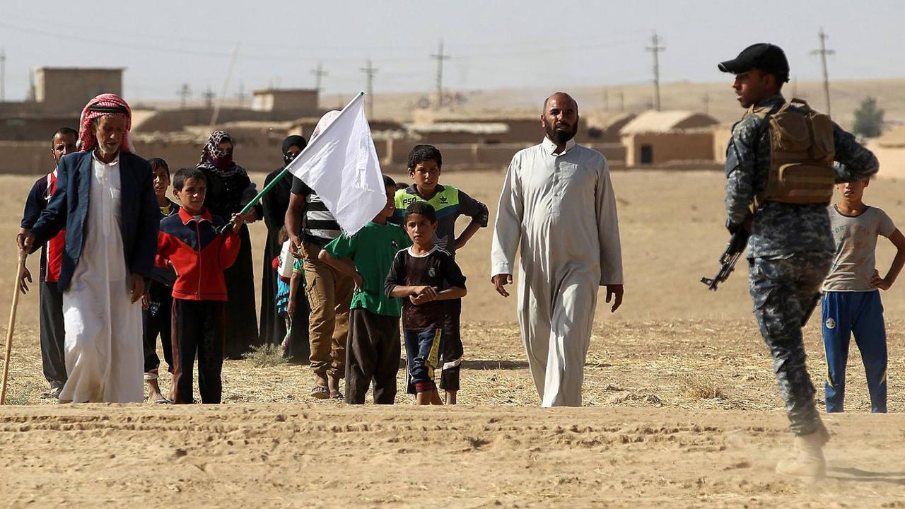 Habitantes de la aldea de Bajwaniyah, 30 km al sur de Mosul, huyen de los combates en dirección a las fuerzas iraquíes que lucha contra el EI. AFP PHOTO / AHMAD AL-RUBAYE