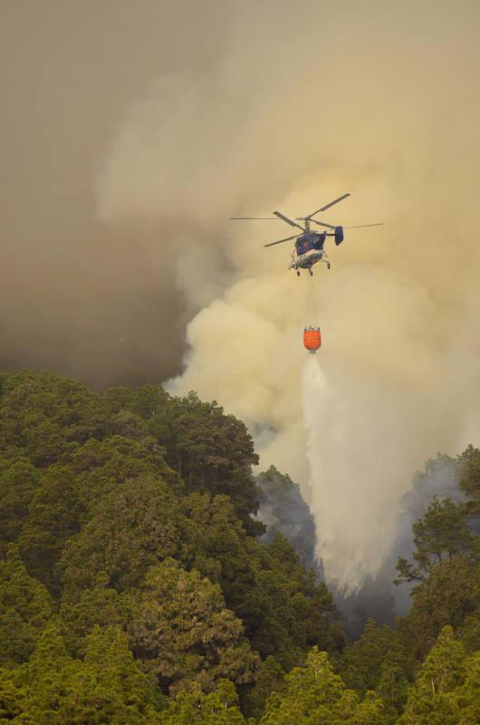 Un helicóptero descarga agua sobre el fuego en el incendio en el municipio de El Paso, en La Palma.