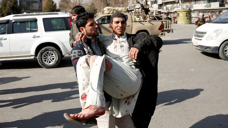 Un hombre acarrea a un herido por una explosión en Kabuil, Afganistán