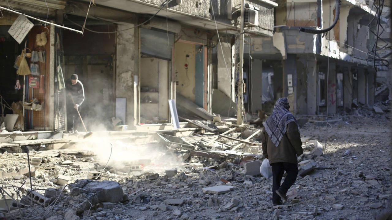 Un hombre camina entre los escombros de un edificio en una calle de Douma, afueras de Damasco