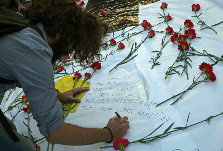 Un hombre escribe en una pancarta de homenaje a Abel Martínez, el profesor asesinado por un alumno de 13 años del instituto Joan Fuster de Barcelona.