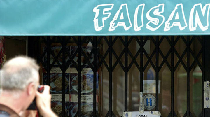 Un hombre fotografía el bar Faisán, que está cerrado