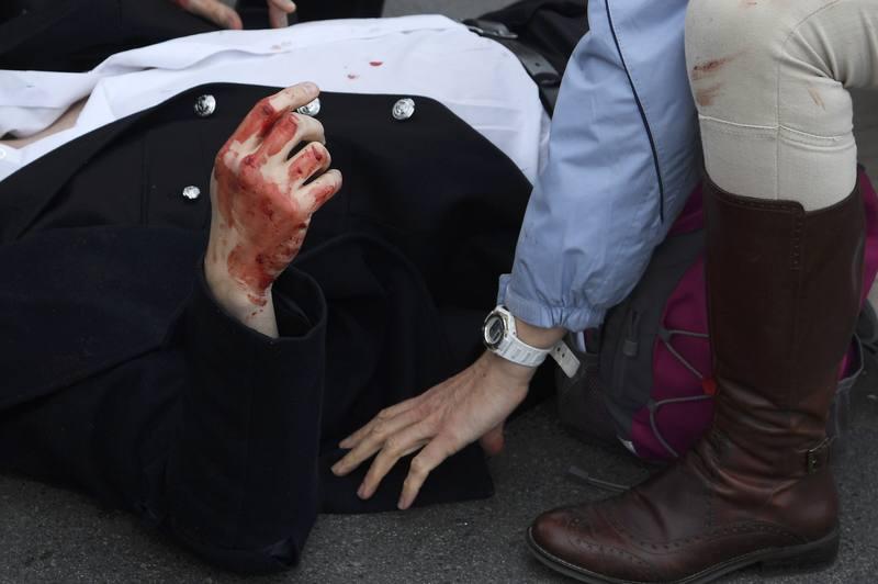 Un hombre herido es asistido sobre el puente de Westminster.