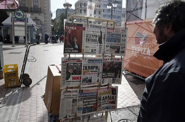Un hombre lee la prensa griega expuesta en un quiosco de Atenas