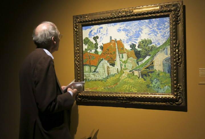 Un hombre observa la obra 'Calle en Auvers' de Vincent Van Gogh, en la exposición 'Van Gogh en Borinage: el nacimiento de un artista, en la ciudad belga de Mons.