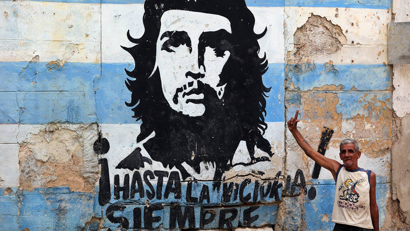 Un hombre posa junto a un grafiti del Che Guevara en La Habana