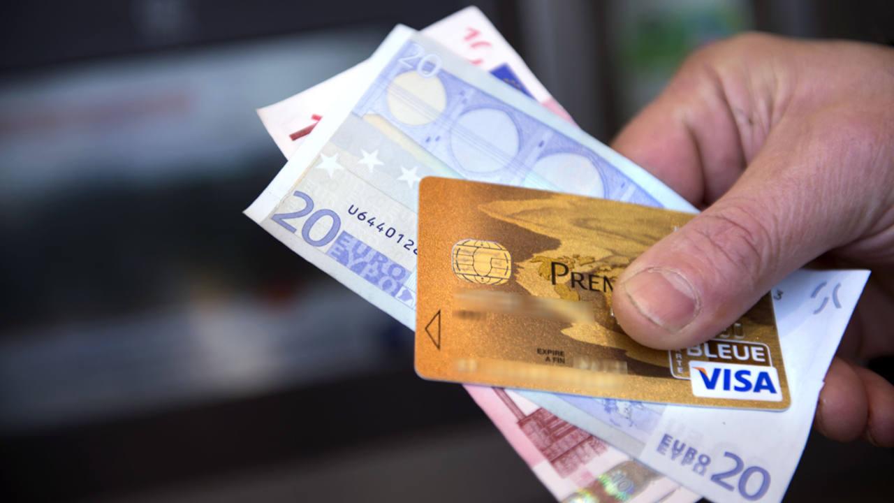 Un hombre sujeta 30 euros y una tarjeta visa