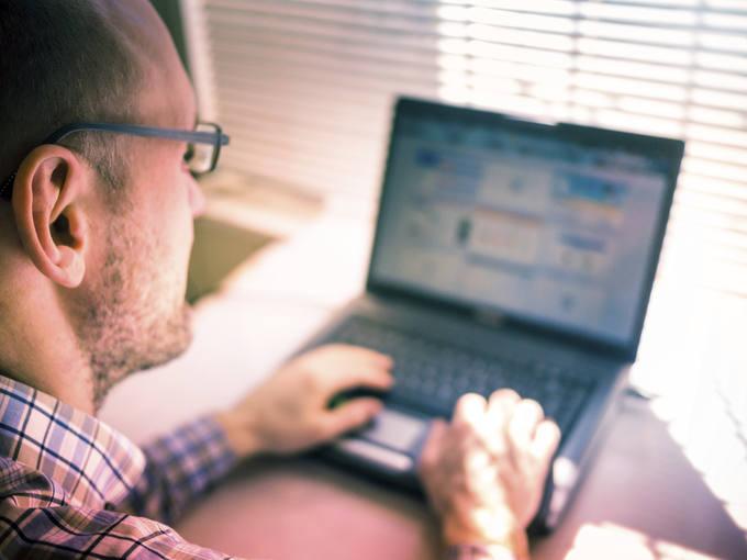 Un hombre trabajando con el ordenador portátil.