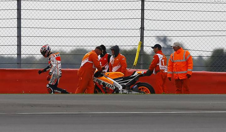 Honda MotoGP rider Marc Marquez of Spain walks away after a fall during the third practice session for the British Grand Prix at the Silverstone Race Circuit
