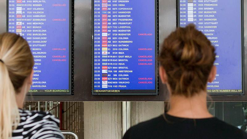 Imagen de archivo en la que varias personas observan un panel informativo del aeropuerto de Palma