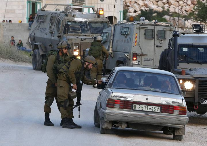 Israeli soldiers stop a car as they search for a missing Israeli near the West Bank city of Hebron