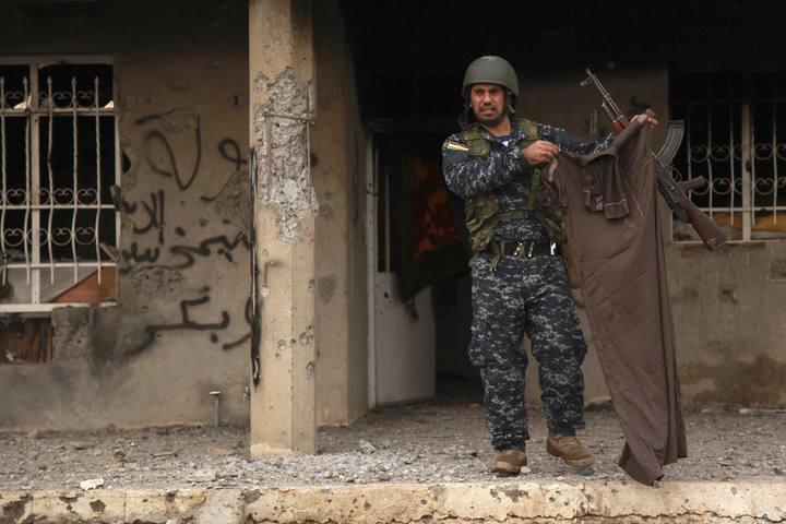 Un kurdo muestra las ropas de un miembro del Estado islámico en Kesarej
